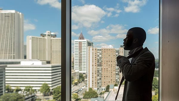 Young man in a suit next to window overlooking the city